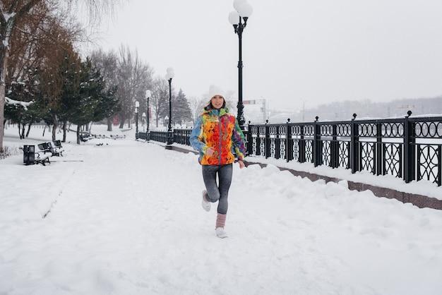 Piękna, młoda dziewczyna biegnie w mroźny i śnieżny dzień. sport, zdrowy tryb życia.