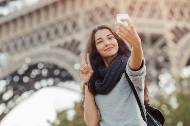 Piękna młoda dziewczyna bierze śmiesznego selfie z jej telefonem komórkowym blisko wieży eifla.
