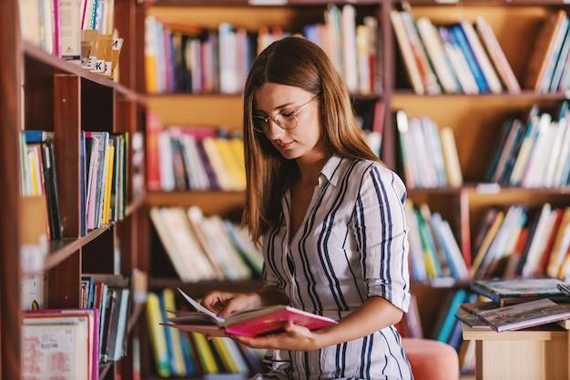 Piękna młoda dziewczyna college'u stojąc w bibliotece i czytając książkę.