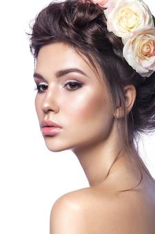 Piękna młoda dziewczyna, czysta skóra, piękny makijaż, fryzury warkocze i kwiaty róży we włosach.