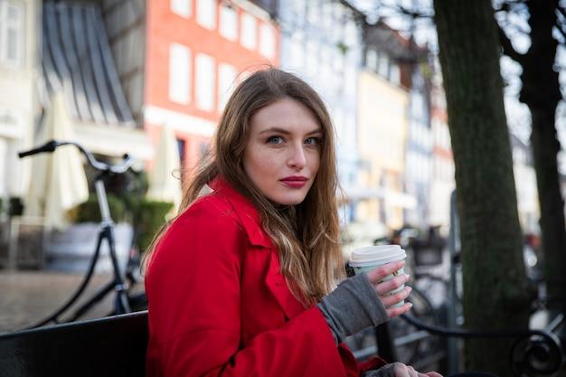 Piękna młoda dziewczyna europejski trzyma filiżankę kawy w zimie, siedząc na ławce. jest zimno.