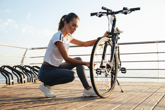 Piękna młoda dziewczyna fitness na zewnątrz, naprawianie roweru, krajobraz morski