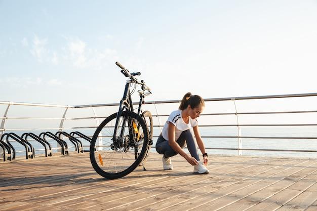 Piękna młoda dziewczyna fitness na zewnątrz z rowerem, morze krajobraz, wiązanie jej sznurowadło