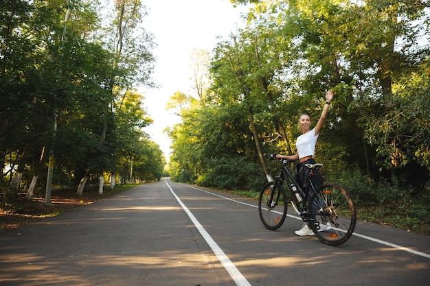 Piękna młoda dziewczyna fitness spaceru z rowerem przy drodze w parku