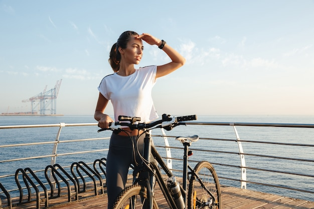Piękna młoda dziewczyna fitness stojący na zewnątrz z rowerem, krajobraz morski