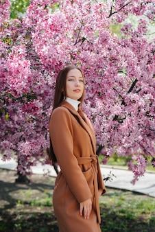 Piękna młoda dziewczyna idzie w dzień wiosny w kwitnącym sadzie jabłkowym. styl życia, rekreacja.