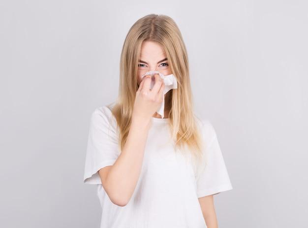 Piękna młoda dziewczyna jest przeziębiona i wydmuchuje nos w serwetkę. pojęcie medycyny i sezonowych przeziębień.