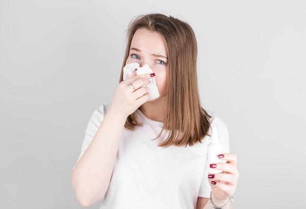 Piękna młoda dziewczyna jest przeziębiona i wydmuchuje nos w serwetkę.