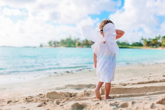 Piękna młoda dziewczyna jest ubranym aniołów skrzydła na plaży
