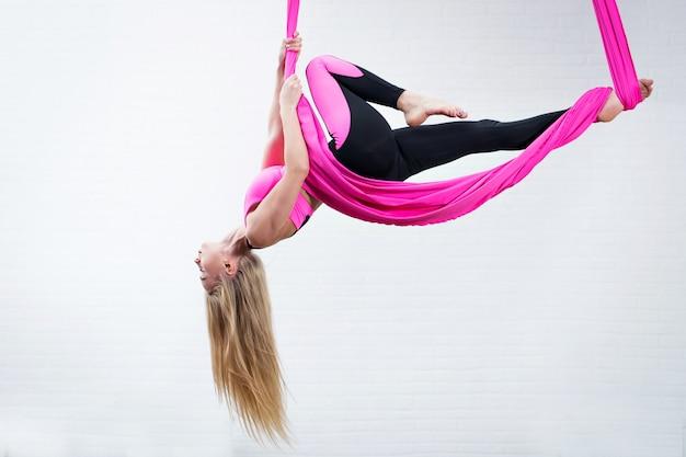 Piękna młoda dziewczyna joga antygrawitacyjna na różowym jedwabnym hamaku podczas robienia.