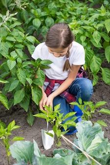 Piękna młoda dziewczyna kopie ziemię uziemiającą na łóżku w ogrodzie warzywnym