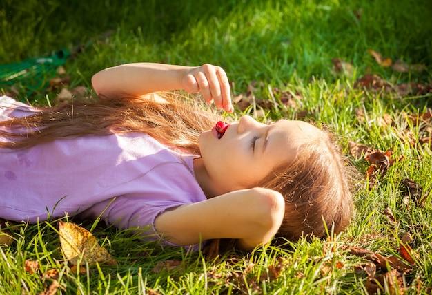 Piękna młoda dziewczyna leżąc na trawie i jedząca wiśnie na świeżym powietrzu