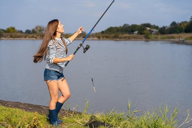 Piękna młoda dziewczyna łowi na jeziorze.