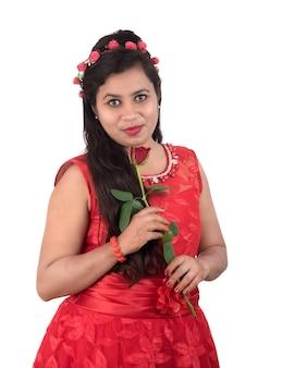 Piękna młoda dziewczyna lub kobieta trzyma i pozowanie z czerwonym kwiatem róży na białym tle