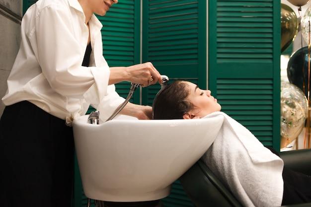 Piękna młoda dziewczyna myje głowę w pięknie. fryzjer myje włosy na widok z boku klienta