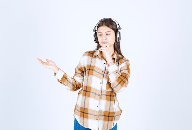 Piękna młoda dziewczyna myśli o czymś w słuchawkach.
