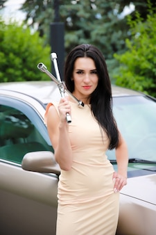 Piękna, młoda dziewczyna na tle samochodu i klucz do kołowrotków