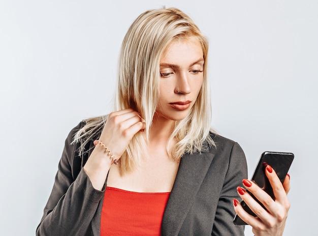 Piękna młoda dziewczyna nieszczęśliwa i trzymająca telefon na szarym tle na białym tle