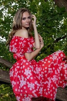 Piękna młoda dziewczyna o doskonałej skórze, z długimi włosami w czerwonej sukience leży na gałęzi drzewa o zrelaksowanym, ospałym wyglądzie.
