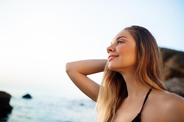 Piękna młoda dziewczyna odpoczywa przy ranek plaży