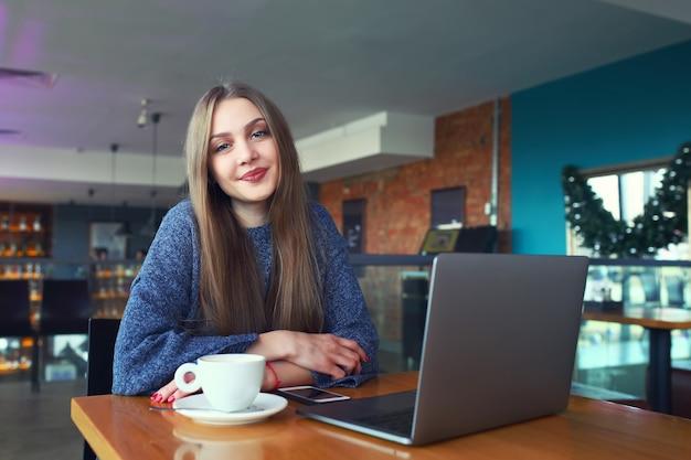 Piękna młoda dziewczyna odpoczywa w kawiarni