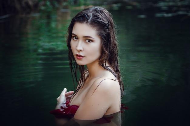 Piękna młoda dziewczyna odpoczywa w wodzie. kobieta na ślepo, pływa w dół rzeki, medytując w wodzie