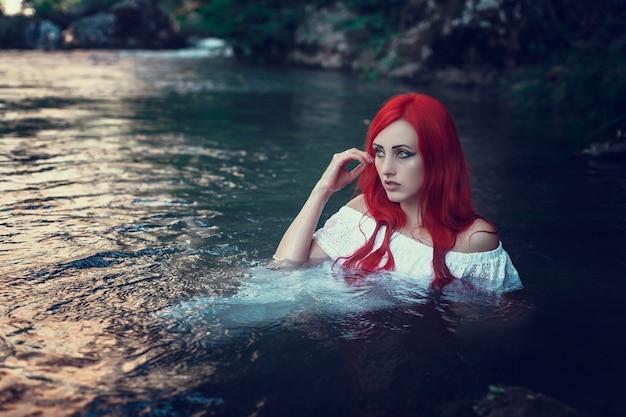 Piękna młoda dziewczyna odpoczywa w wodzie. młoda kobieta w białej sukni siedzi na kamieniu na środku potoku.
