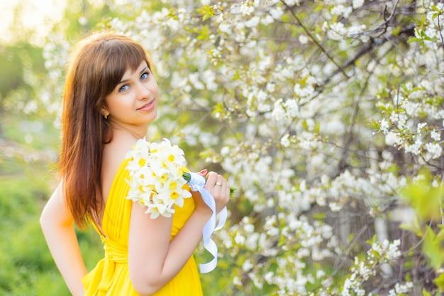 Piękna młoda dziewczyna ono uśmiecha się z bukietem kwiaty outdoors w wiośnie
