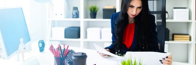 Piękna młoda dziewczyna patrzy przez dokumenty, siedząc w biurze przy stole.