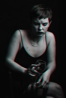 Piękna, młoda dziewczyna pije czerwone wino i jest smutna