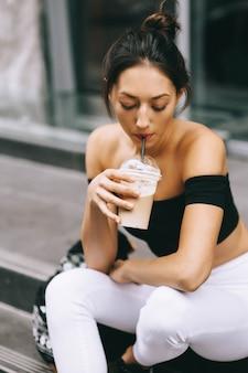 Piękna młoda dziewczyna pije kawę w mieście