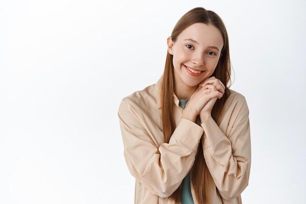 Piękna młoda dziewczyna podziwia coś słodkiego, patrzy z podziwem i czułością, uśmiecha się głupio, stoi szczęśliwa przy białej ścianie.