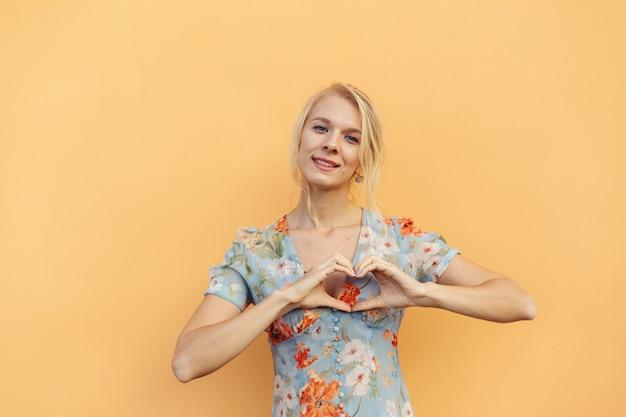 Piękna, młoda dziewczyna pokazuje kształt serca z rękami na pomarańczowym tle pastelowych.