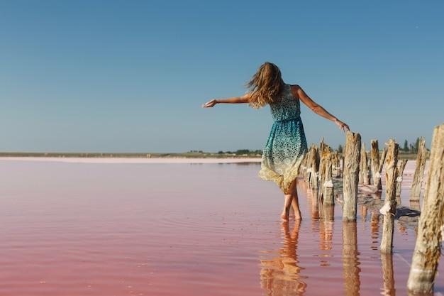 Piękna, młoda dziewczyna pozuje na słonym jeziorze w pobliżu starego drewnianego mostu, genichesk, ukraina. portret szczupła kobieta w krótkiej sukience w pobliżu różowego morza. podróżowanie po ukrainie