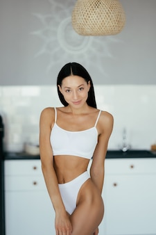 Piękna, młoda dziewczyna pozuje w bieliźnie w kuchni