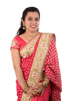 Piękna, młoda dziewczyna pozuje w indyjskich tradycyjnych sari na białym tle.