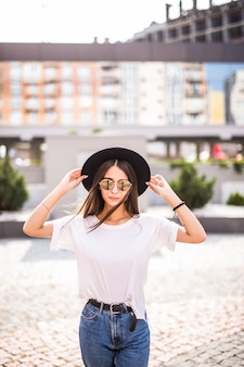 Piękna młoda dziewczyna pozuje w kapeluszu na ulicie