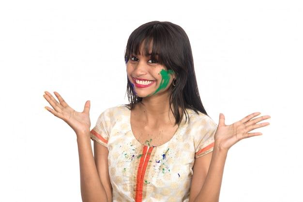 Piękna młoda dziewczyna pozuje z kolorową twarzą przy okazji holi festiwalu
