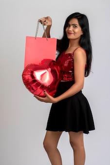 Piękna, młoda dziewczyna pozuje z torby na zakupy i balon na szaro