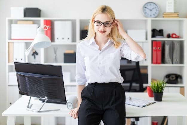 Piękna młoda dziewczyna pracuje w jaskrawym biurze przy komputerowym biurkiem.