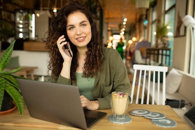 Piękna młoda dziewczyna pracuje w kawiarni z laptopemfemale freelancer trzymając telefon łączący się z internetem przez komputer robi zakupy online
