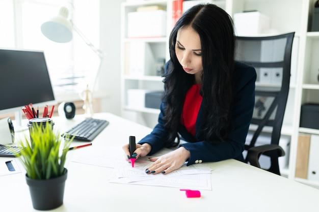 Piękna młoda dziewczyna pracuje z dokumentami w biurze przy stołem. dziewczyna podkreśla ważne punkty w dokumencie za pomocą różowego markera.