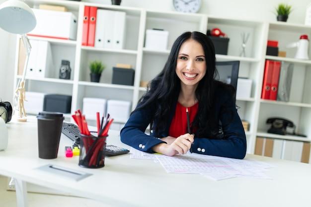 Piękna młoda dziewczyna pracuje z dokumentami w biurze przy stołem i trzyma ołówek w jej ręce