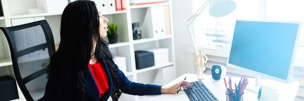 Piękna młoda dziewczyna pracuje z komputerem i dokumentami w biurze przy stołem.