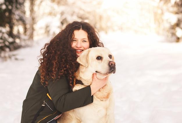 Piękna, młoda dziewczyna przytula psa labrador w zimie w przyrodzie