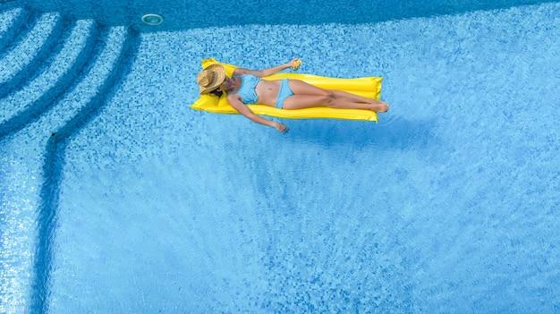 Piękna młoda dziewczyna relaks w basenie, kobieta pływa na nadmuchiwanym materacu i dobrze się bawi w wodzie na rodzinne wakacje, tropikalny ośrodek wypoczynkowy, widok z lotu ptaka z drona