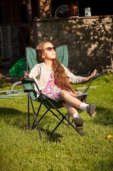 Piękna młoda dziewczyna relaks w fotelu na trawie w słoneczny dzień