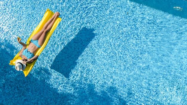 Piękna młoda dziewczyna relaksuje w basenie, kobieta pływa na nadmuchiwanym materacu i ma zabawę w wodzie na wakacjach rodzinnych