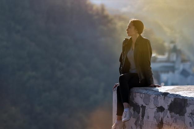 Piękna młoda dziewczyna siedzi na przepaści i marzy. stopy na klifie. słoneczny dzień