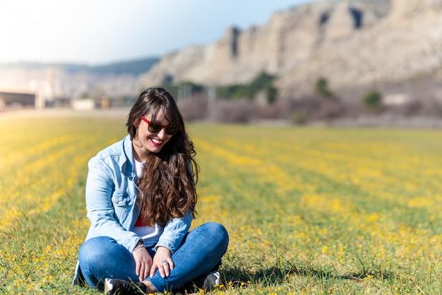 Piękna młoda dziewczyna siedzi na trawie na zewnątrz.